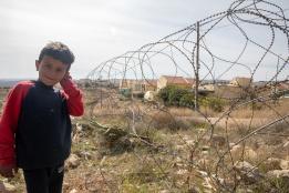 A child standing by Isareli settlement in Um Al-Kheir Village, South Yatta, Hebron.