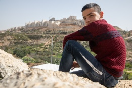 a boy in Wadi Foukin, Bitar Illit settlement in the background