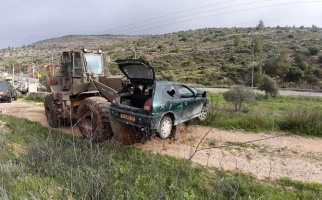 An Israeli bulldozer transporting the confiscated Palestinian car after the accident