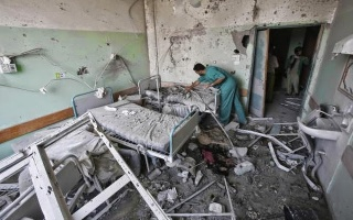 A_Palestinian_medic_inspects_a_damaged_room_at_Al-Aqsa_hospital